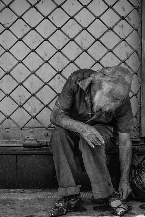 Homeless man sitting near metal fence on street