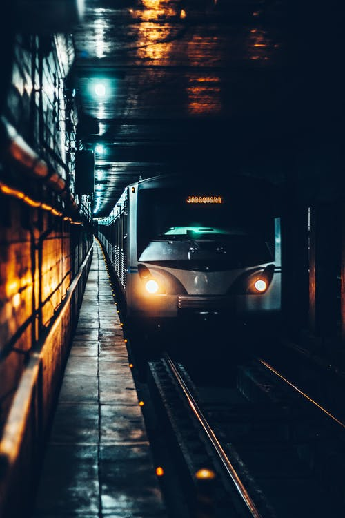 Modern electric train with glowing headlights riding on railway and approaching underground station