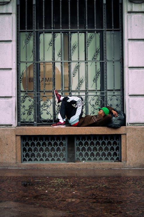 Man resting on windowsill of old building on street