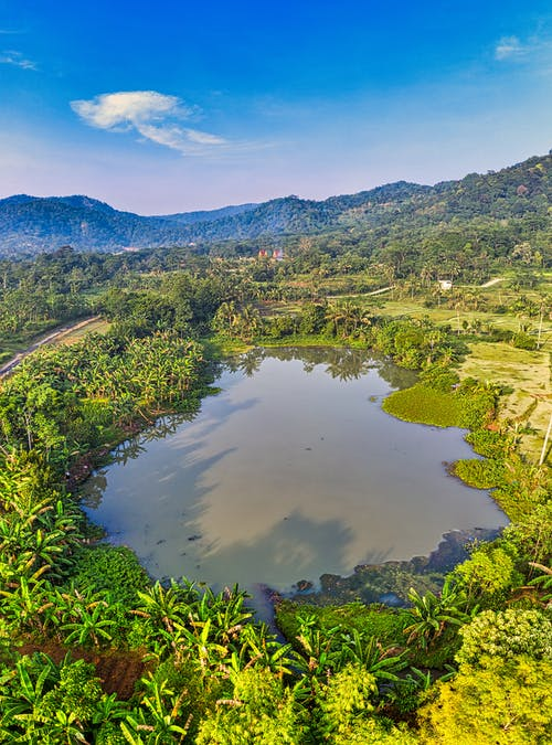 Small pond in mountainous valley covered with tropical trees