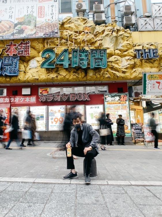 Ethnic man in mask sitting against crowded sidewalk