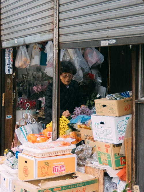 Asian female seller standing at counter of street store with variety of flowers and goods