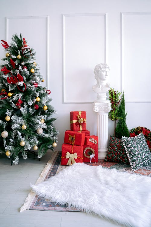 Green Christmas Tree With Baubles and Gift Boxes In A Room