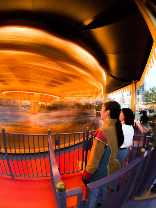 Women standing near fast carousel in amusement park