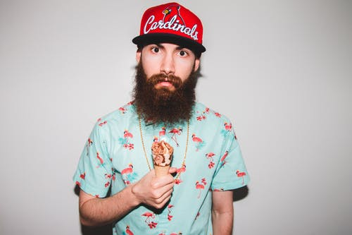 Young male hipster in cap and stylish t shirt with ice cream looking at camera against gray background
