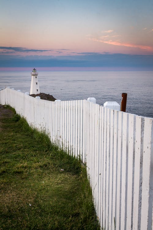 Lighthouse placed on seacoast behind fence