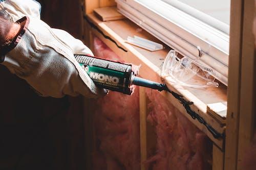Crop unrecognizable workman in glove applying caulk from bottle on seam during window montage work in building