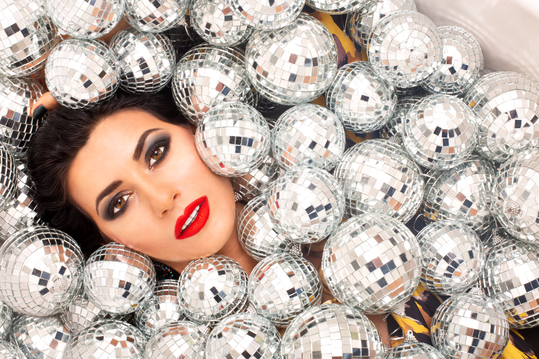 charming woman lying under disco balls
