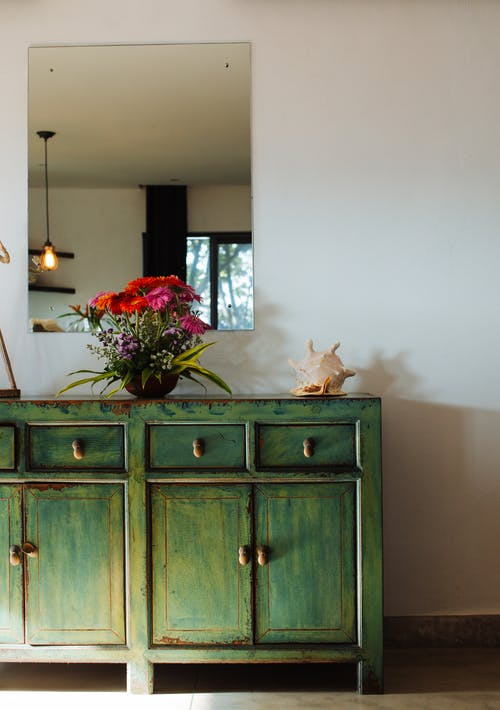 Vase with Flowers on Green Wooden Cabinet