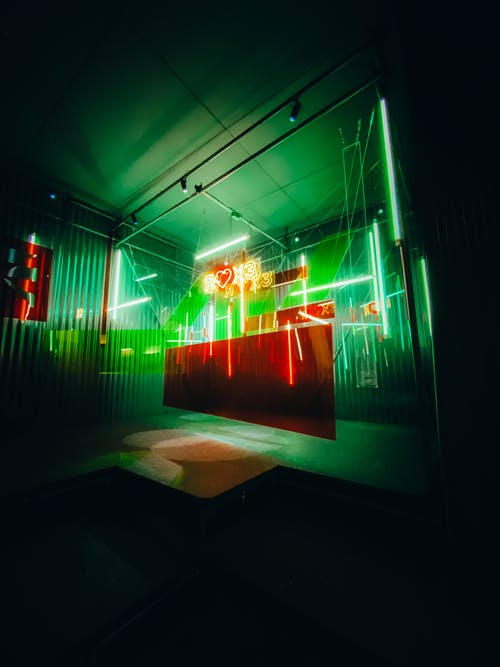 Modern interior with art installation of colorful glasses in neon lights and heart sign in darkness
