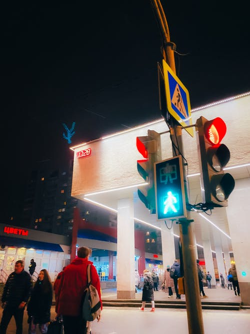 People walking near illuminated traffic light placed on concrete pillar with pedestrian crossing sign located in city street at night in Russia