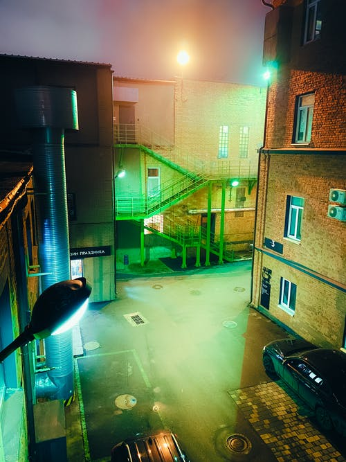 Empty industrial district with parked cars and illumination