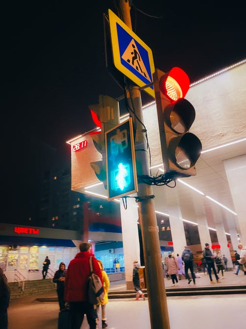 From below of people walking near modern city building located on city street near glowing traffic light located on pillar with pedestrian crossing sign at night