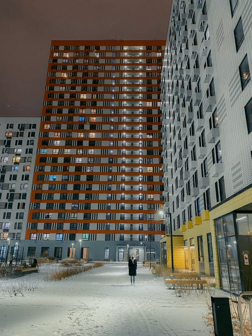 Person standing on street with contemporary residential buildings in winter time