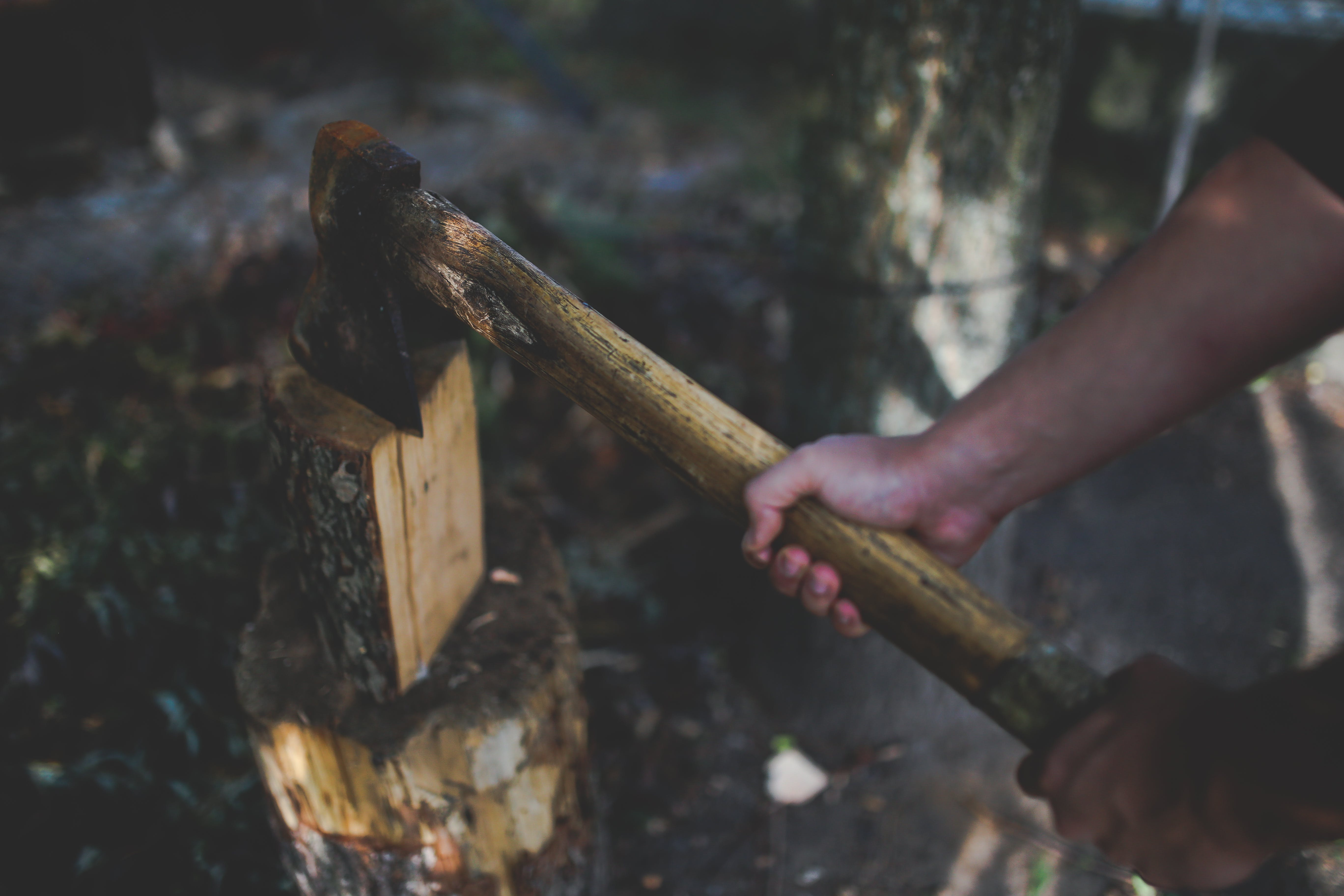 A man holds an old, worn axe