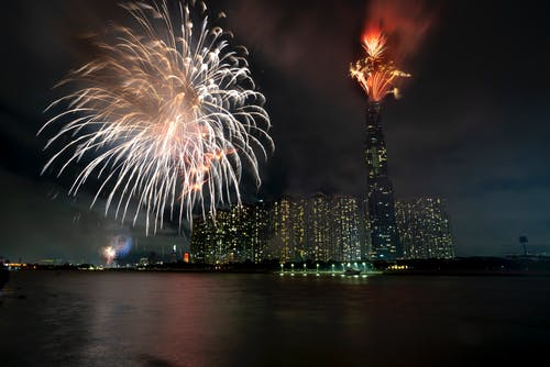 Bright colorful fireworks shining on dark sky over calm sea and illuminated modern houses at night time during holiday celebration