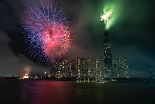 Festive night in big megapolis with glowing windows in skyscrapers and shining colourful fireworks in dark sky