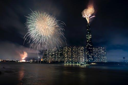 Big megapolis celebrating holiday with fireworks in sky