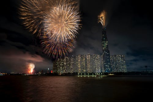 Beautiful shiny fireworks exploding in night sky over big modern megapolis with high skyscrapers