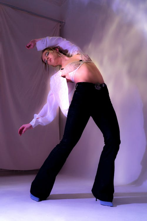 Full body of young bending back female dancing  modern dance in black trousers white shirt and bra