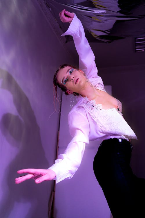 Woman in bra and shirt dancing in studio