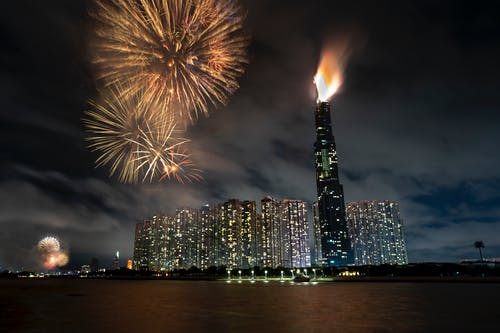Night cityscape with illuminated skyscrapers and fireworks near river