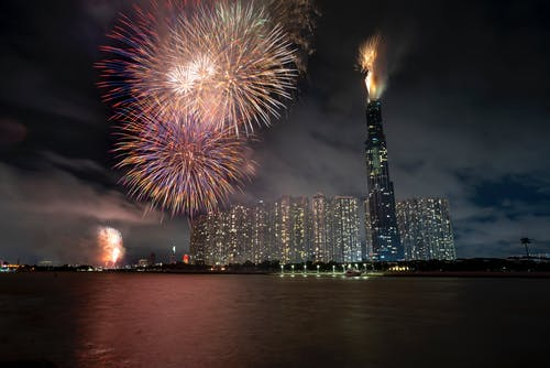 Illuminated skyscrapers with tall building named Landmark 81 in Vietnam in Ho Chi Minh City near black river with colorful fireworks under dark cloudy sky at night