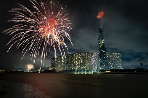 Cityscape with illuminated fireworks and skyscrapers near river at night