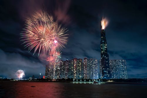 Illuminated skyscrapers in Vietnam in Ho Chi Minh City with tall building named Landmark 81 near black water and colorful fireworks in twilight under dark cloudy sky