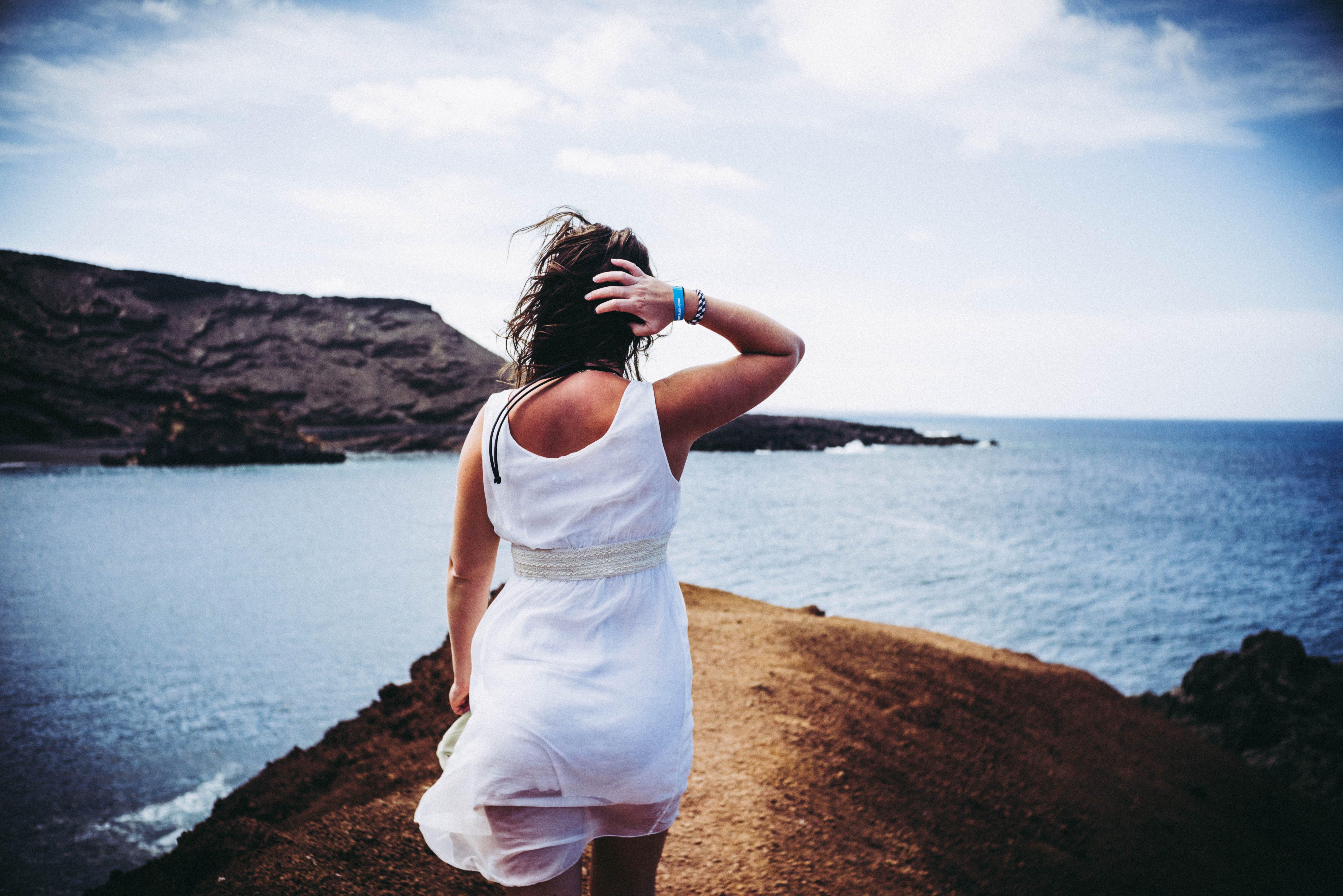 Woman Wearing White Sleeveless Mini Dress on Top of Brown Sand Near Body of Water