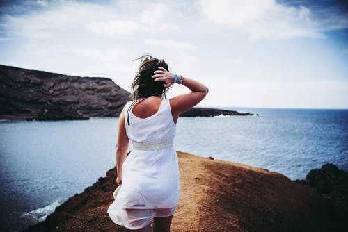 Woman Wearing White Sleeveless Mini Dress on Top of Brown Sand Near Body of Water