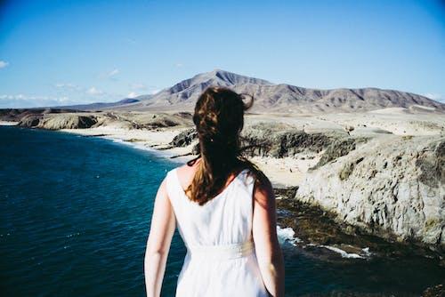Gratis arkivbilde med fjell, hav, jente, kjole