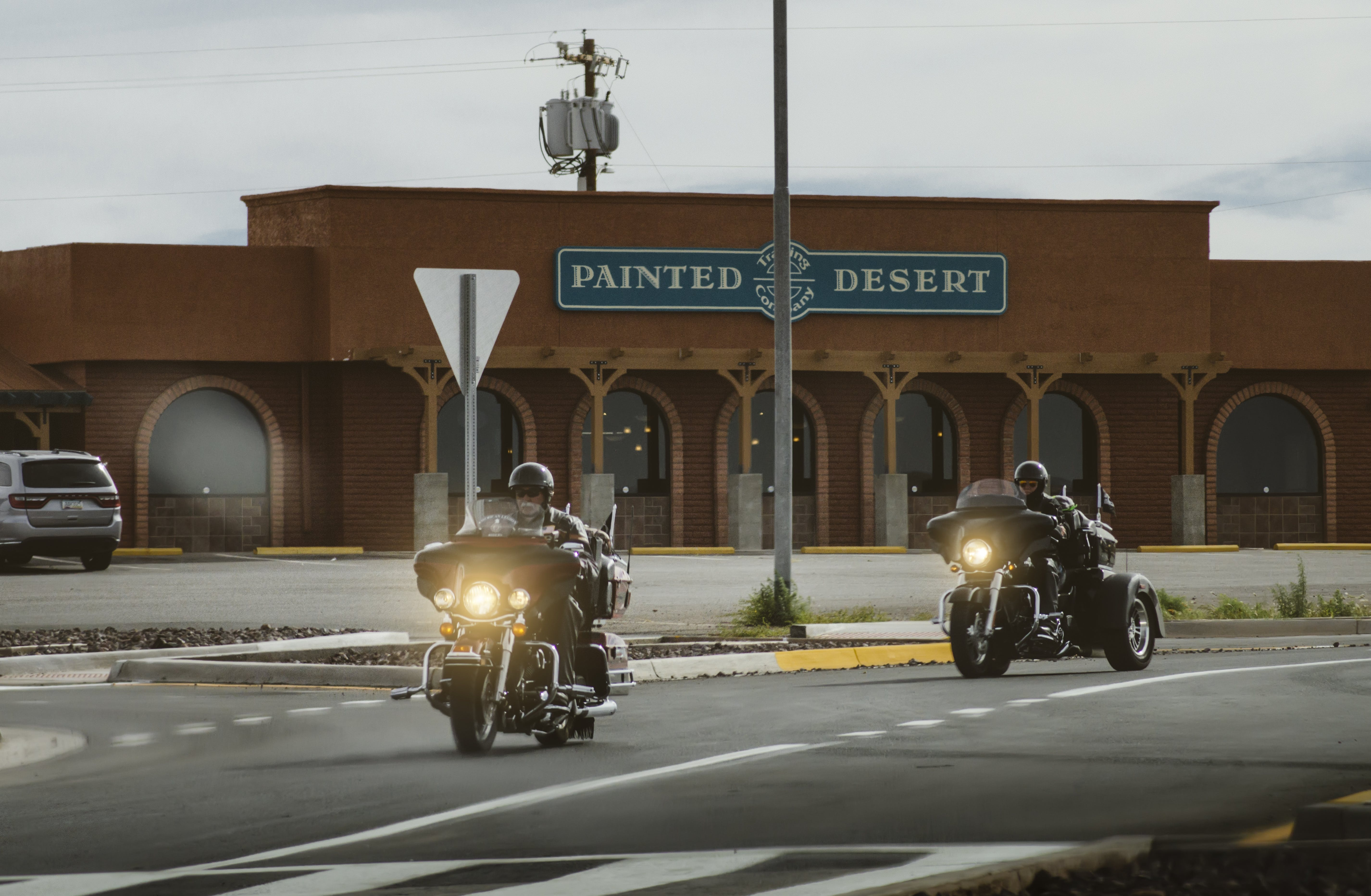 Two Men Riding on Touring Motorcycle Near Painted Desert Store