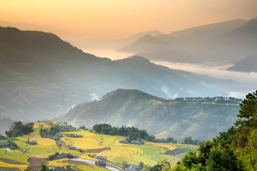 Picturesque view of green valley with green trees and bushes growing on slopes of mountain ridge against cloudy sky