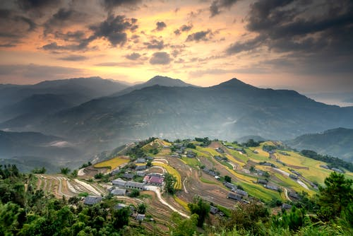 Breathtaking scenery of spacious green highlands with small rural settlement surrounded by abundant agricultural fields under colorful cloudy sky