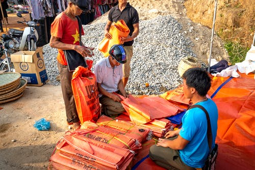 Asian men buying plastic bags in local street market