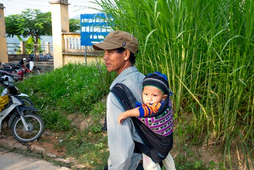 Back view content Asian male in casual wear and cap carrying cute baby on back carrier while standing in lush village
