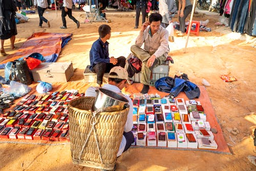 From above of anonymous ethnic male locals sitting on chairs on sandy ground and selling various smartphones on bazaar