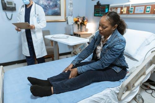 Woman in Blue Denim Jacket and Black Denim Jeans Sitting on Hospital Bed
