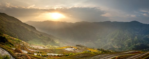 Breathtaking scenery of grassy hills and rice fields under bright sky in sunny summer morning