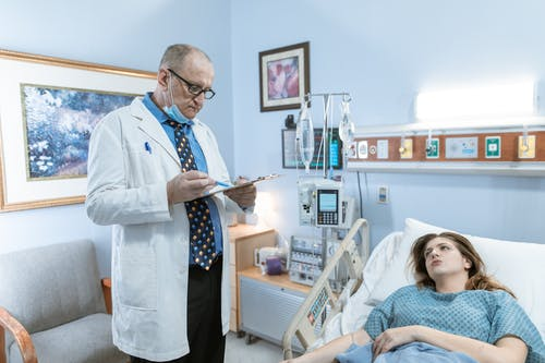 A Physician in White Coat Checking Up on His Patient