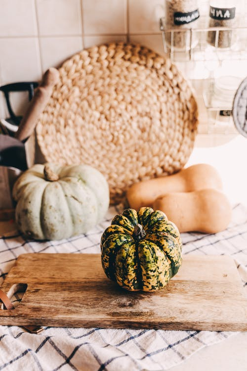 A Fresh Pumpkin on a Wooden Chopping Board