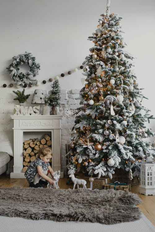 A Child Playing Near A Christmas Tree