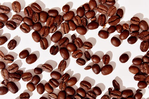 Close-Up Photo of Aromatic Brown Roasted Coffee Beans on White Surface
