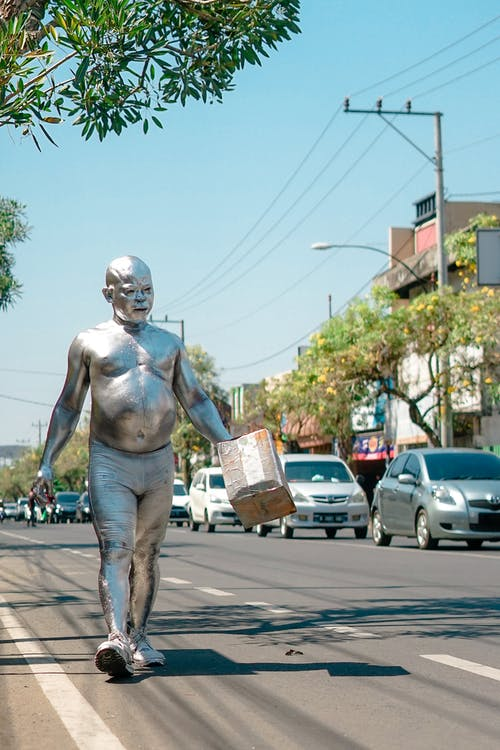 Eccentric man covered with paint strolling on street