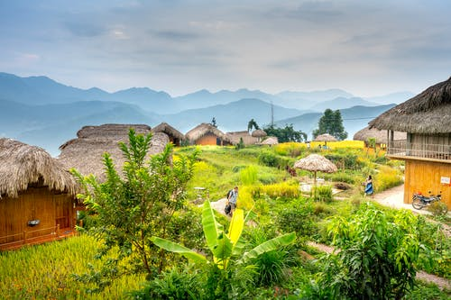 Anonymous tourists strolling in remote exotic hotel with bungalows in green grassy hills under bright sky in daytime
