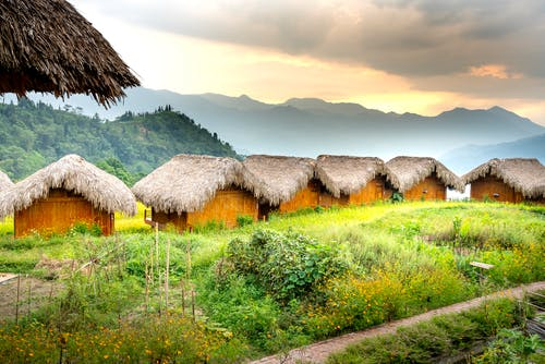 Bungalows in village near green hills