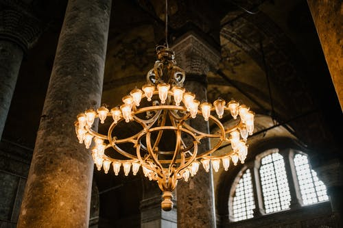 Low angle of old lighting up chandelier hanging from dome with pillars in eastern ancient religious cathedral