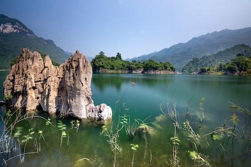 Breathtaking landscape of lake with rocks near green hills