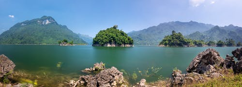 Landscape scenery of lake with rocky coast with grass and green hills with bushes and trees in sunny summer day under blue cloudless sky